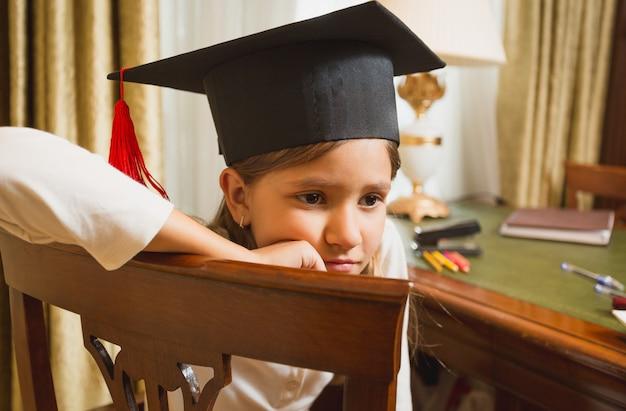 Ritratto del primo piano della bambina premurosa in cappello di graduazione che posa sulla sedia