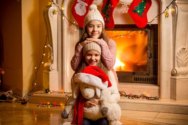 Ritratto del primo piano di due belle ragazze in maglioni seduti al caminetto a casa