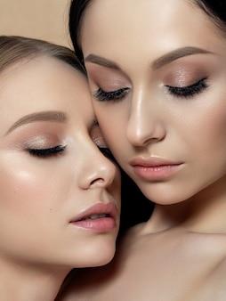 Closeup ritratto di due giovani belle donne. colori beige cremosi. trucco nudo.