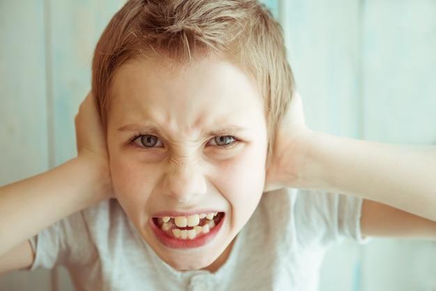 Il ritratto del primo piano infelice ha infastidito il ragazzo che copre le orecchie con le mani