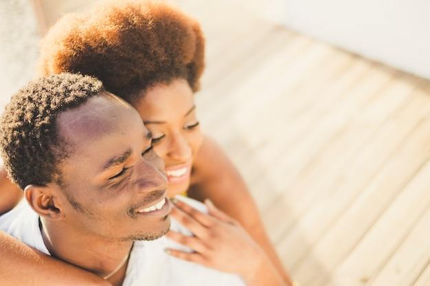 Ritratto del primo piano visto dall'alto per due maschi e femmine di razza africana sorridenti e felici insieme. abbraccio e amore per la giovane coppia millenaria posano per una foto con un grande bel sorriso big