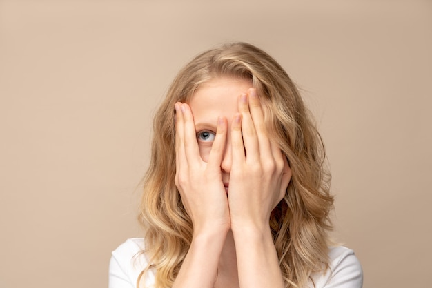 Closeup ritratto donna che copre la mano sul viso, sbirciando con un occhio. isolato sulla parete beige.