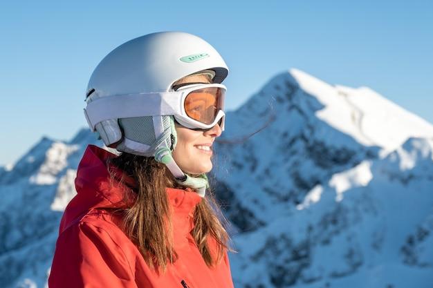 Closeup ritratto di donna in casco e maschera con sulla stazione sciistica. concetto di avventura invernale