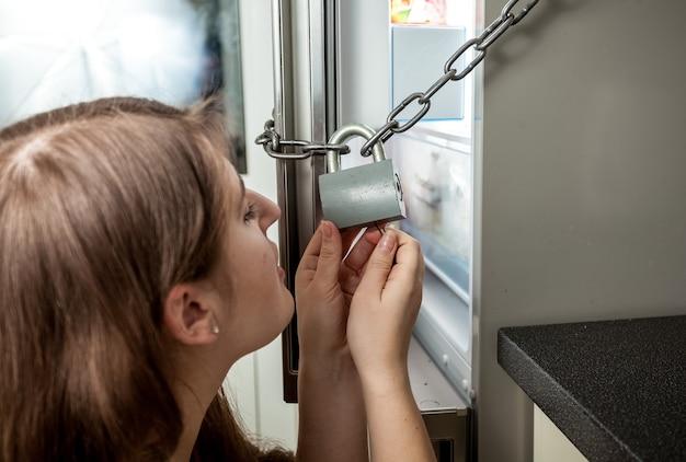Ritratto del primo piano della donna che guarda dentro il frigorifero chiuso a chiave