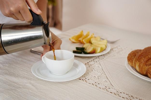 Closeup ritratto di una donna che versa il caffè da una caffettiera geyser in una tazza bianca sul tavolo.