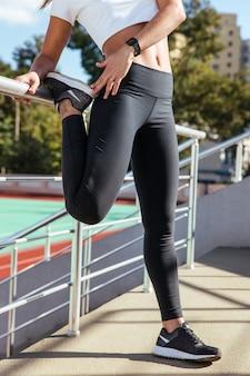 Closeup ritratto di una donna che allunga le gambe all'aperto sullo stadio