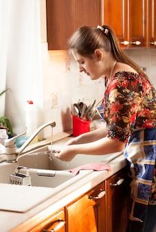Ritratto del primo piano della donna che lava i piatti sulla cucina