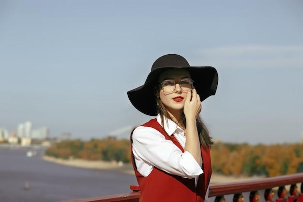 Il ritratto del primo piano della donna meravigliosa indossa il costume rosso, il cappello nero, gli occhiali alla moda. spazio per il testo
