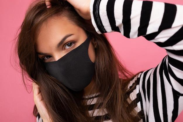 Ritratto del primo piano di giovane donna attraente del brunet nella maschera di protezione mediacale isolata sopra la parete del fondo. protezione contro il covid-19