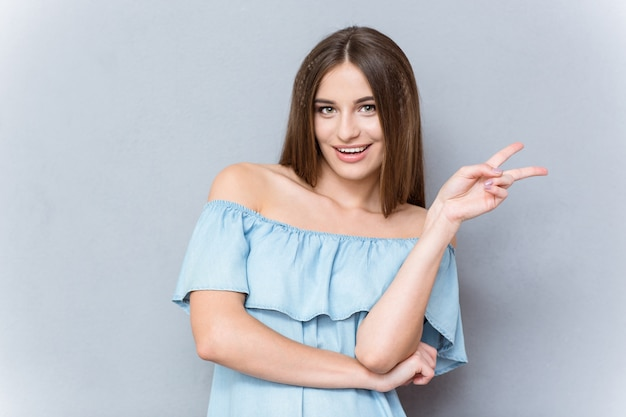Ritratto del primo piano di giovane bella donna emozionante sicura sorridente felice che mostra il segno di vittoria
