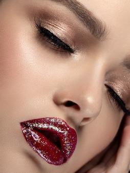 Closeup ritratto di giovane bella donna con labbra rosse scintillanti moda trucco