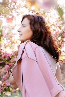 Primo piano ritratto di una giovane ragazza riccia con i capelli scuri sullo sfondo di alberi rosa in fiore