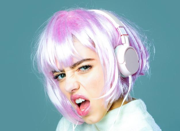 Closeup ritratto di giovane donna emotiva o ragazza sexy con parrucca di capelli rosa glamour con auricolare musicale