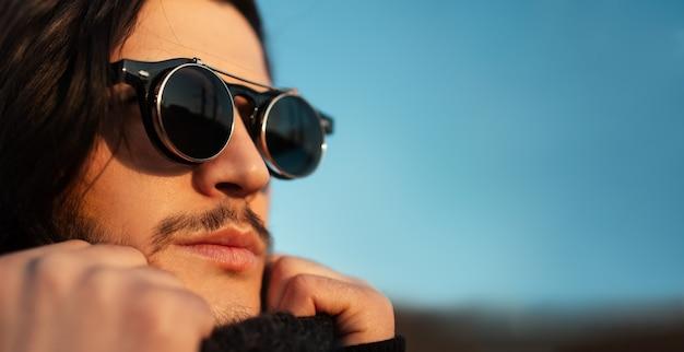 Closeup ritratto di giovane ragazzo con i capelli lunghi che indossa occhiali da sole rotondi hipster e sciarpa. cielo blu sullo sfondo. vista panoramica del banner con spazio di copia.