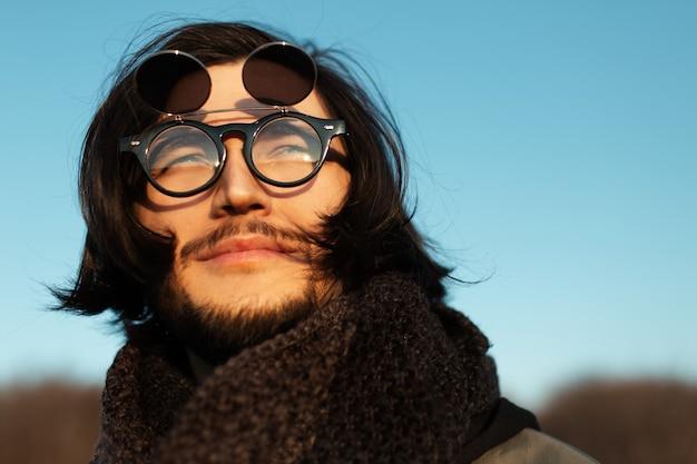 Closeup ritratto di giovane ragazzo con i capelli lunghi che indossa occhiali da sole rotondi hipster e sciarpa. cielo blu sullo sfondo.