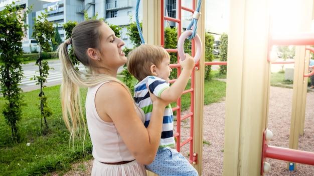 Ritratto del primo piano di giovane madre che aiuta e tiene il suo piccolo figlio appeso e oscillante su anelli sportivi a palyground. bambini attivi che fanno sport