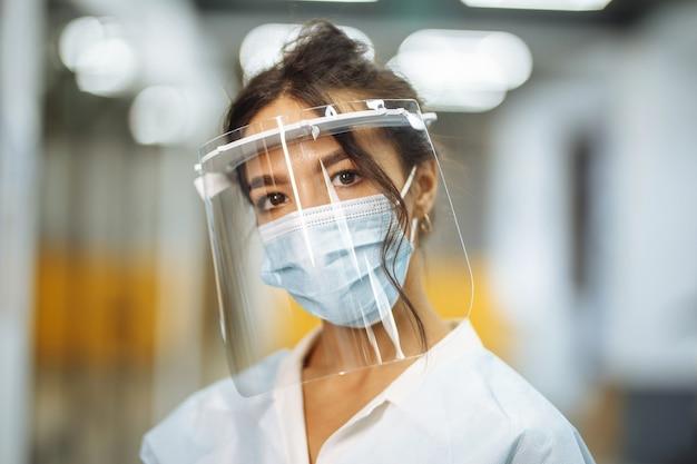 Closeup ritratto di una giovane infermiera che indossa una visiera protettiva e una maschera medica in piedi nel corridoio dell'ospedale. prevenzione del coronavirus durante l'epidemia di pandemia mondiale. concetto di assistenza sanitaria.