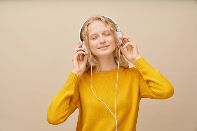 Closeup ritratto di giovane donna ha chiuso gli occhi ascoltando musica tramite le cuffie sulla parete beige