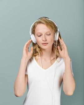 Closeup ritratto di giovane donna ha chiuso gli occhi ascoltando musica tramite le cuffie
