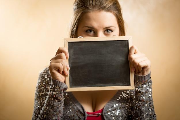 Ritratto del primo piano della giovane donna che si nasconde dietro la lavagna