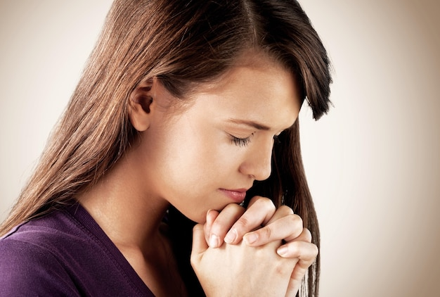 Ritratto del primo piano di una giovane donna che prega