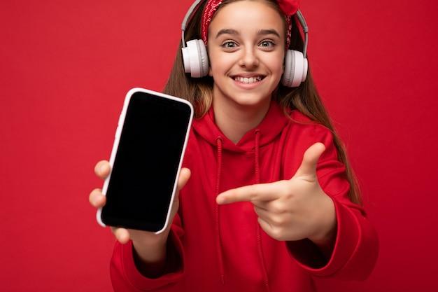 Primo piano positivo sorridente carina ragazza bruna che indossa una felpa con cappuccio rossa isolata su sfondo rosso red