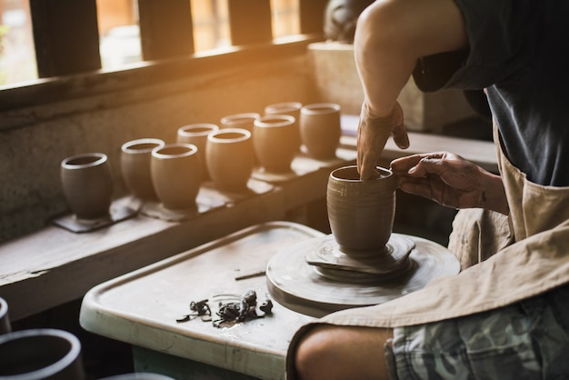 Le mani del vasaio del primo piano che modellano l'argilla molle per fare un vaso di terra