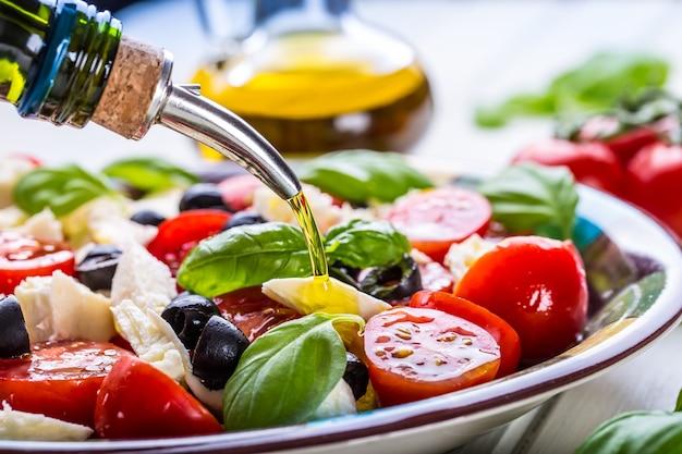 Primo piano di versare l'olio d'oliva nell'insalata caprese italiana.