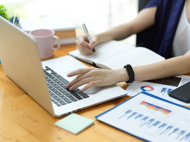 Primo piano donna d'affari professionale che lavora in ufficio, lavora al laptop e prende appunti, analisi aziendale