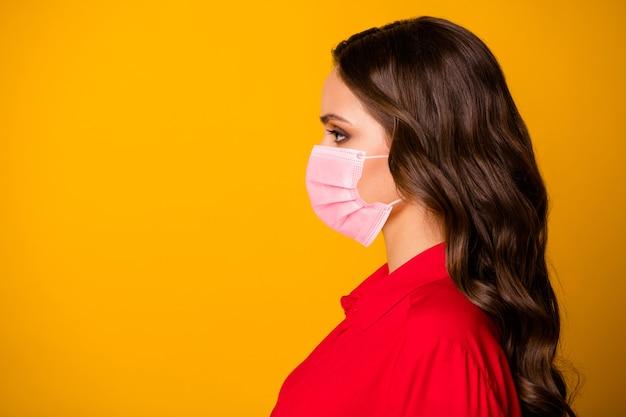 Foto del profilo del primo piano di una bella donna d'affari riccia piuttosto sbalorditiva persona prepotente guardare spazio vuoto indossare maschera medica ufficio lusso camicia rossa isolato sfondo giallo vivido colore