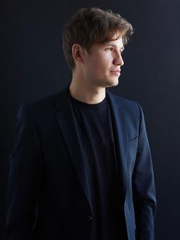 Closeup ritratto di profilo di un attraente giovane uomo d'affari in giacca, su sfondo nero.