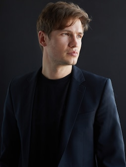 Closeup ritratto di profilo di un bel giovane uomo d'affari in giacca, su sfondo nero.