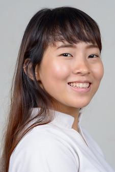 Vista di profilo del primo piano di giovane donna asiatica felice che guarda l'obbiettivo
