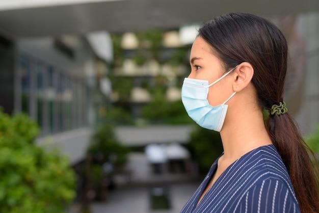Primo piano vista di profilo della giovane donna di affari asiatica con maschera per la protezione dallo scoppio del virus corona in città