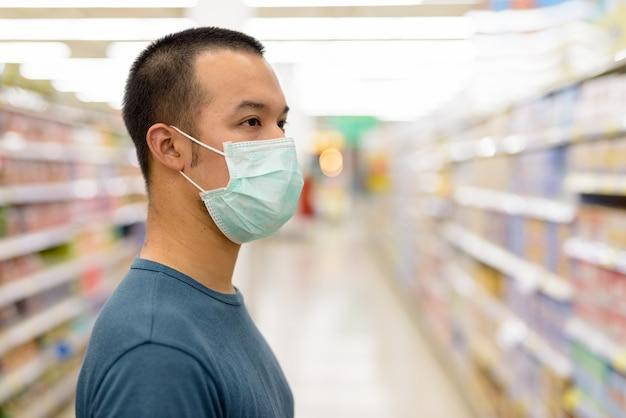 Vista di profilo del primo piano del giovane uomo asiatico con la maschera di acquisto con la distanza al supermercato