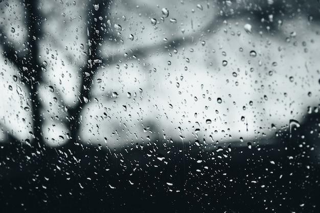 Primo piano di gocce di pioggia sulla finestra di vetro, gocce d'acqua con riflessione e rifrazione della luce, paesaggio autunnale scuro sfocato, sfondo astratto bianco e nero.