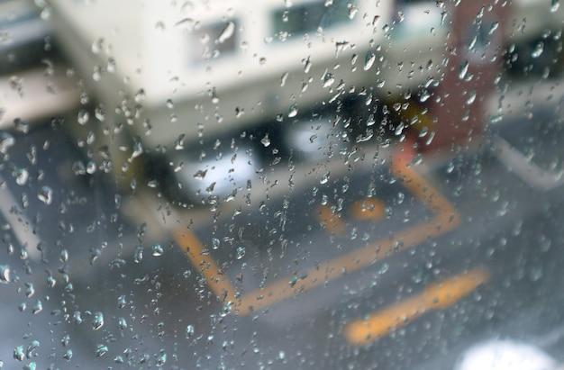 Primo piano le gocce di pioggia sul vetro della finestra con vista aerea sfocata del parcheggio sullo sfondo