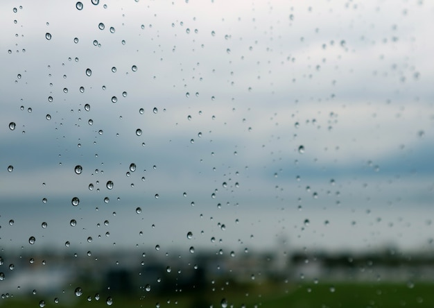 Gocce di pioggia del primo piano sulla finestra con il fuoco selettivo