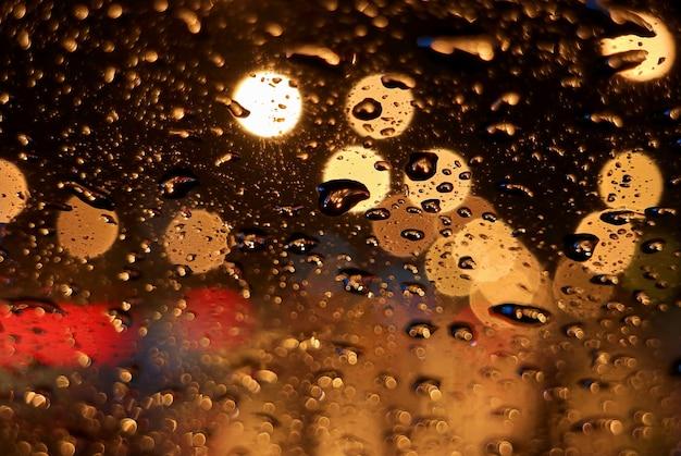 Gocce di pioggia in primo piano sulla superficie del parabrezza dell'auto, con luci stradali urbane sfocate di notte