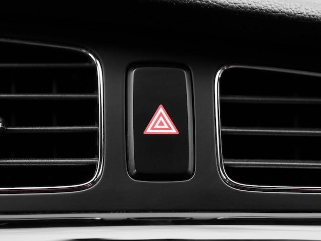 Pulsante interruttore luce di emergenza rosso primo piano all'interno di un'auto moderna.