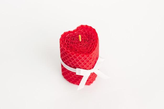 Primo piano di una candela di cera d'api naturale decorativa di colore brillante rosso a forma di cuore con nastri di pizzo e un aroma di miele per interni isolati su una parete bianca