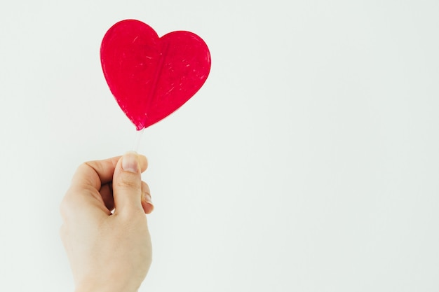 Primo piano del lecca-lecca a forma di cuore rosso con sfondo bianco