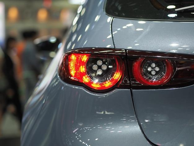 Lato posteriore della luce rossa del primo piano di colore grigio brillante della nuova automobile nel concetto di trasporto di evento di motor show