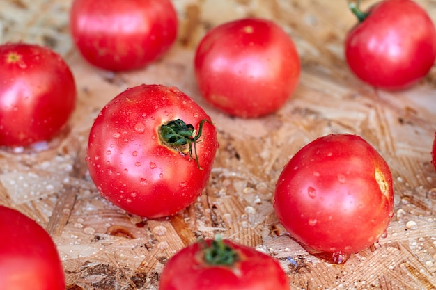 Pomodori freschi maturi rossi del primo piano sulla tavola del compensato