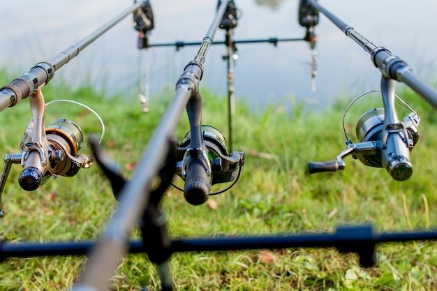 Primo piano di una canna da pesca con mulinello su un puntello e acqua