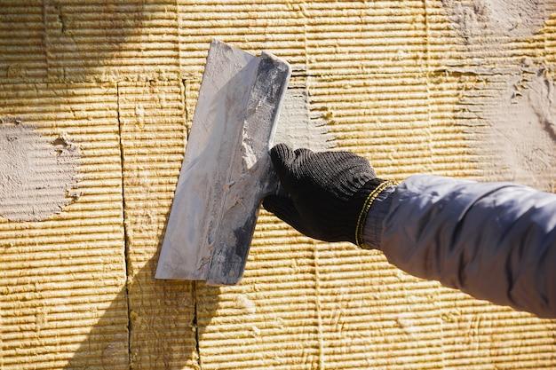 Primo piano del riparatore in uniforme, costruttore professionale che lavora utilizzando attrezzature da costruzione. processo di costruzione, ristrutturazione dell'appartamento, riparazione, costruzione. colorare, misurare, preparare la base.