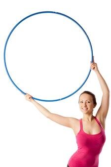 Primo piano della donna relativa alla ginnastica ritmica con il cerchio in su e che si appoggia con garbo a destra.