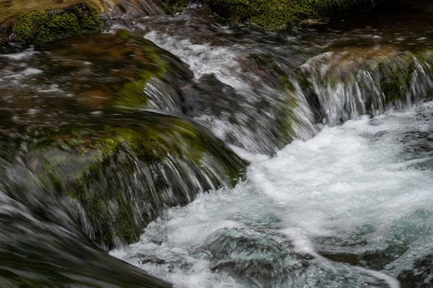 Primo piano del fiume di montagna del flusso del fiume tra grandi pietre