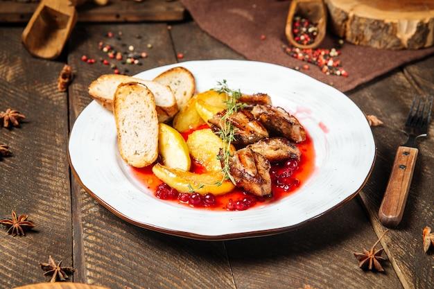 Primo piano sul pollo arrosto con toast di patate e salsa di mirtilli rossi