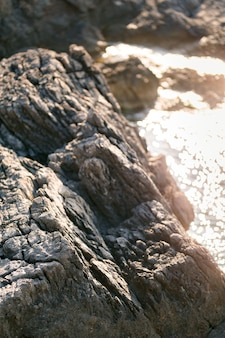 Primo piano della costa rocciosa della luce solare del mare e della superficie dell'acqua del bokeh